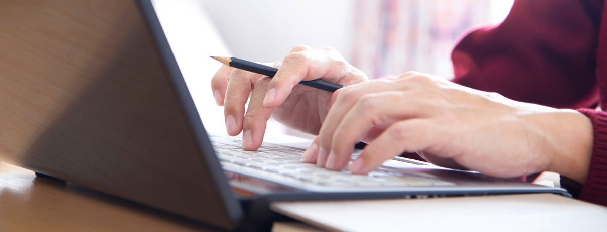 Person writing while on computer